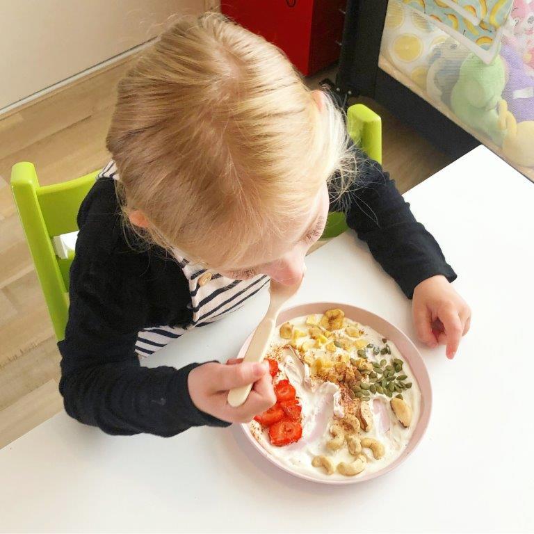 kind eet kwark met gedroogde vruchten en zaden
